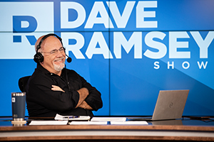 Dave Ramsey smiling and talking to a caller on his radio show
