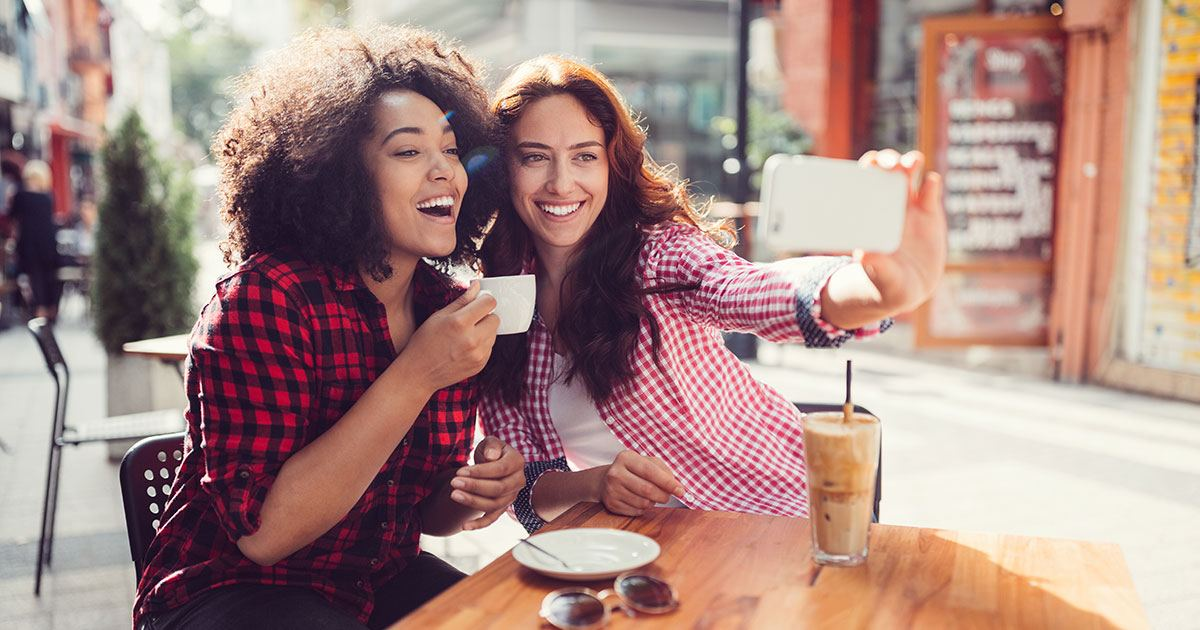 Two women having coffee together pause to take a selfie with their phone.