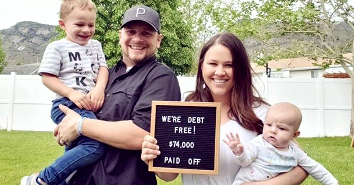 A couple and their two children holding a sign that says