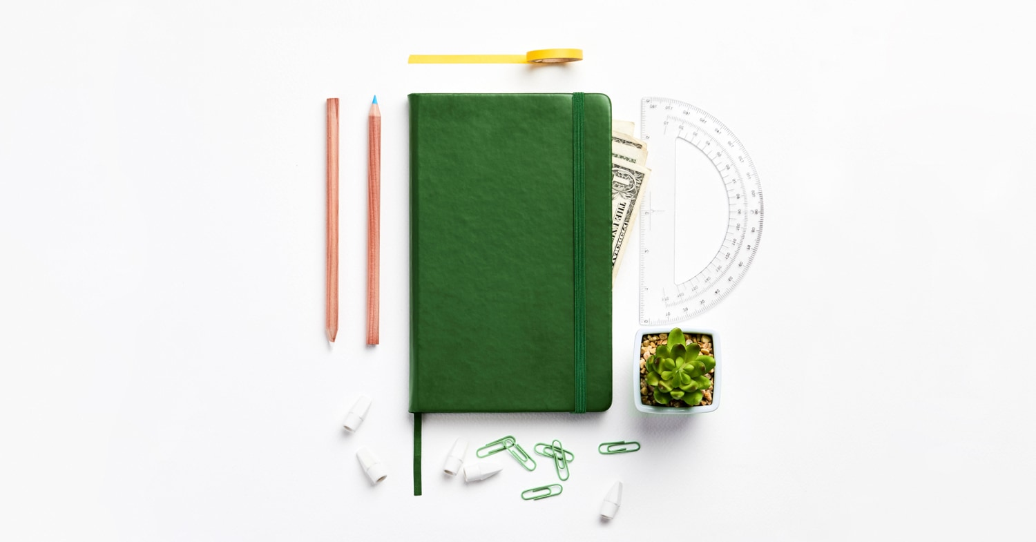 Moleskine notebook with protractor, paper clips, and money