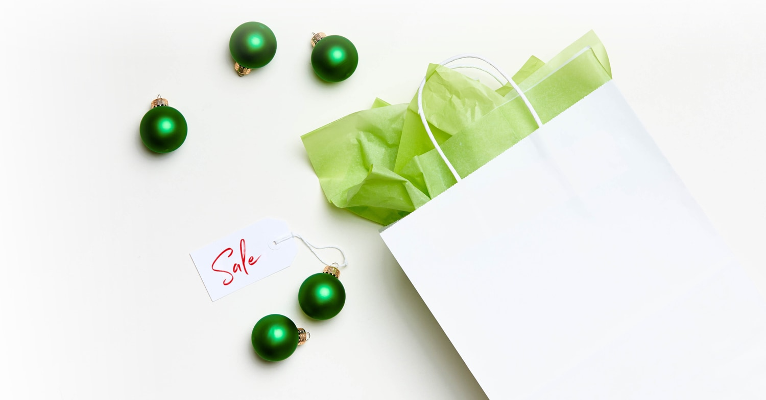 Green ornaments around a white gift bag
