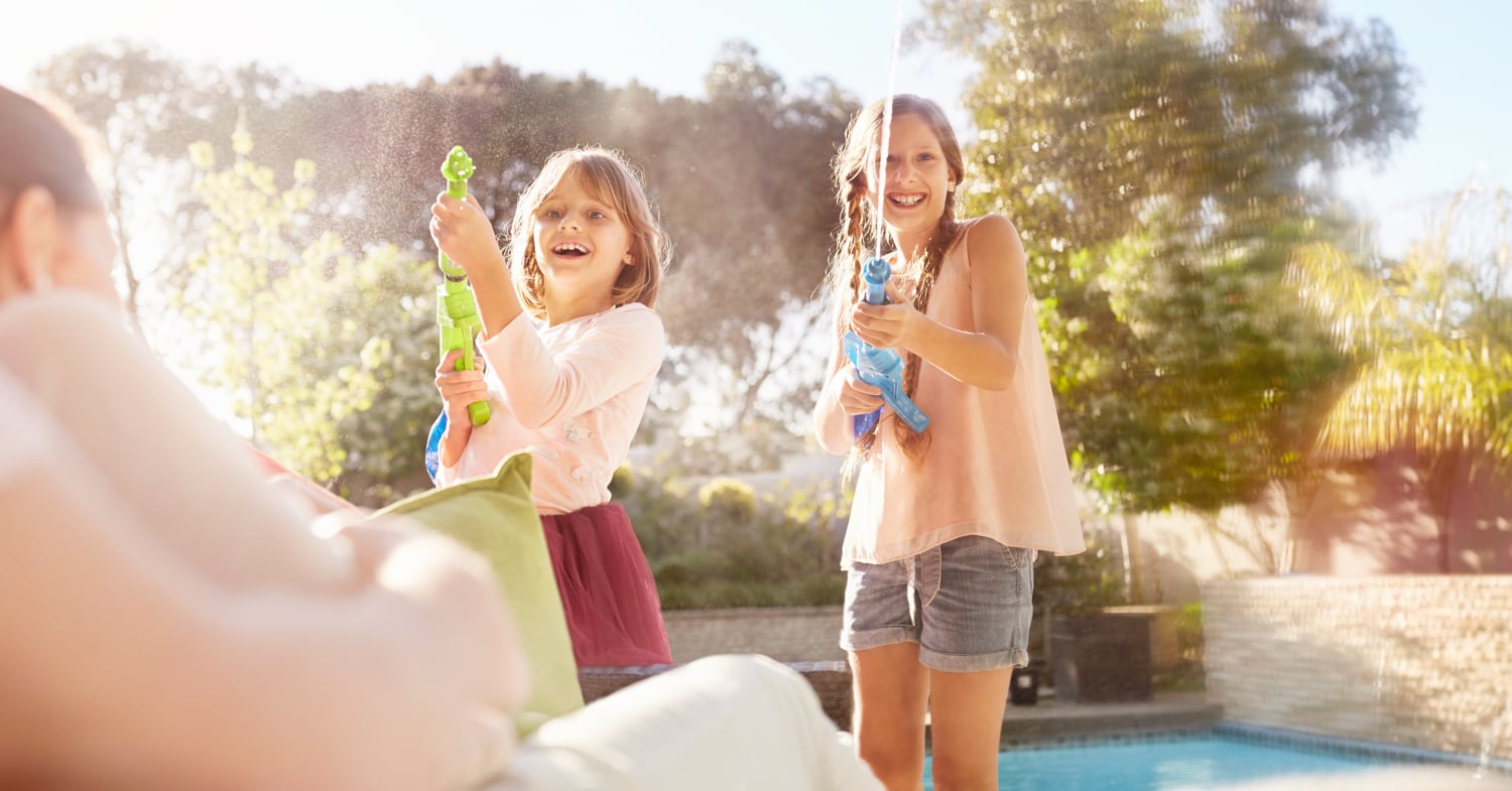 Two girls playing with water guns in a backyard