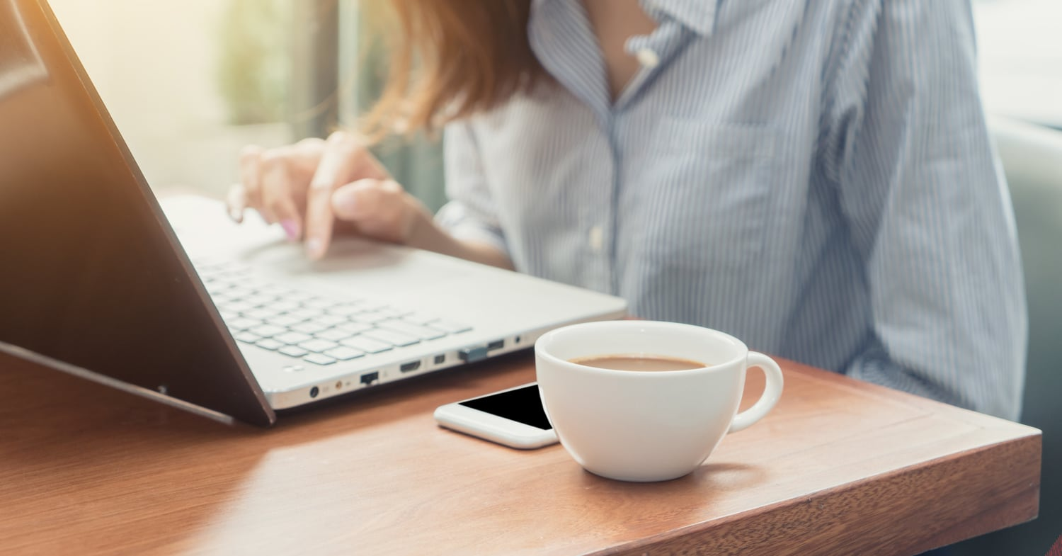 Woman at computer with phone and coffee