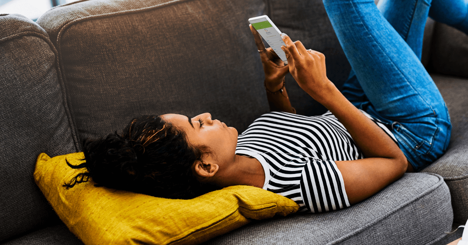 Woman laying on couch budgeting with budget app