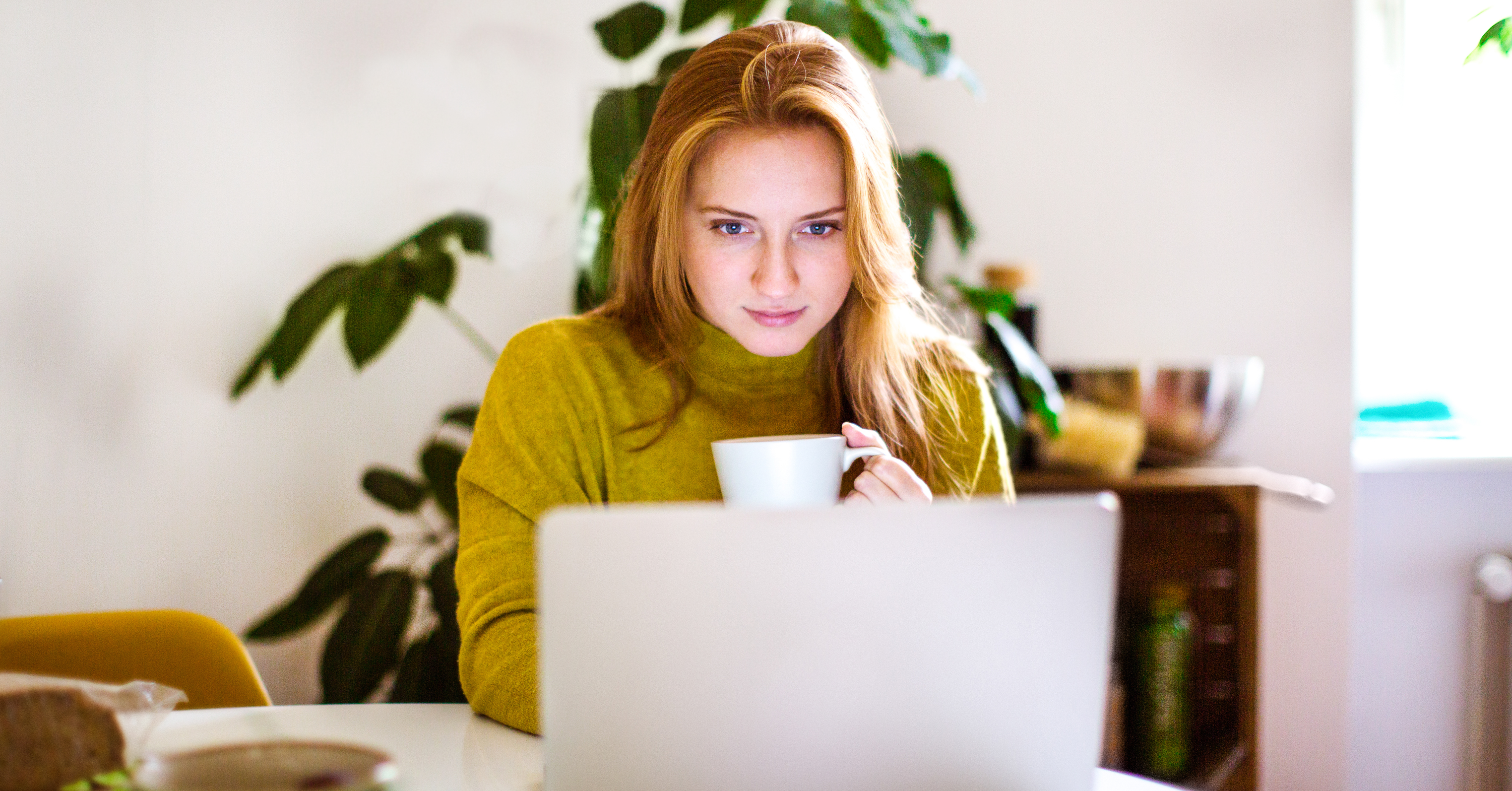 Woman holding a coffee mug looking at a laptop computer