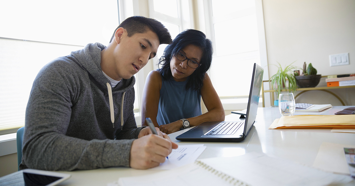 mom and son look over school documents in home