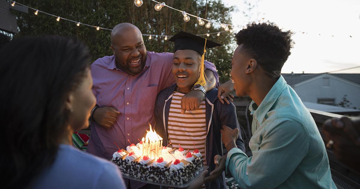 family celebrates teen grad with cake