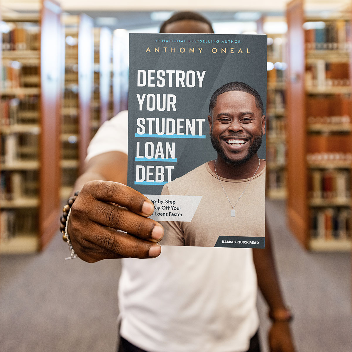 Man holding destroy your student loan debt book