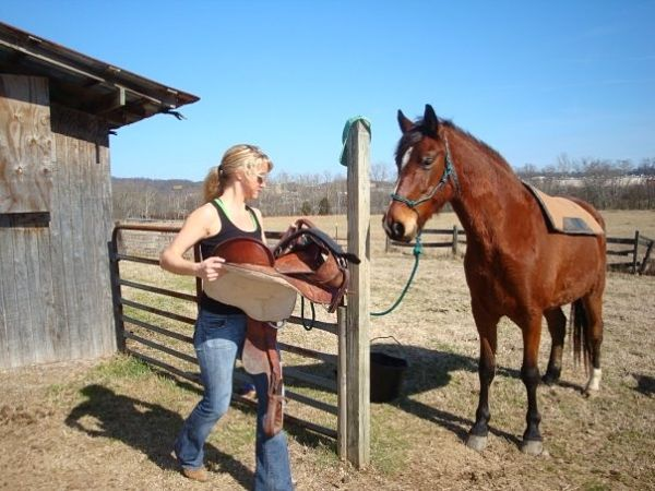 Christy Wright putting a saddle on a horse