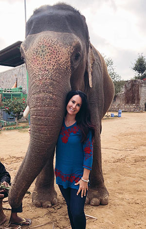 Everyday millionaire Christy T. poses with an elephant.
