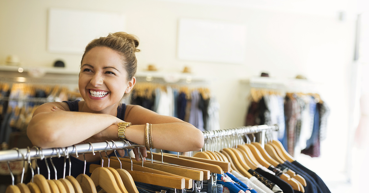 girl leaning on rack of pants in retail store smiling