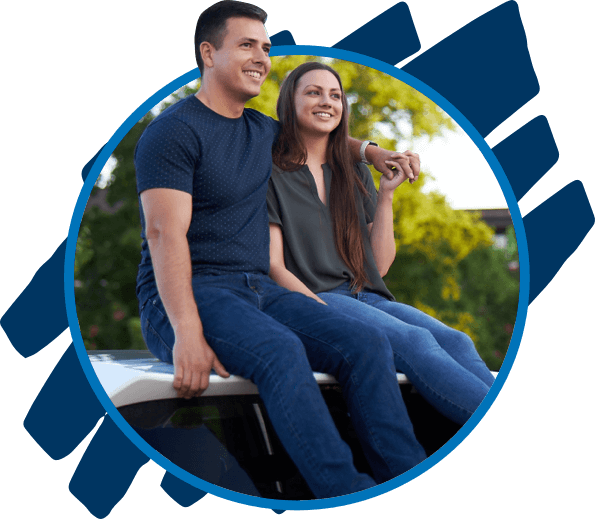 Millennial couple sitting on the roof of a car and looking into the distance.